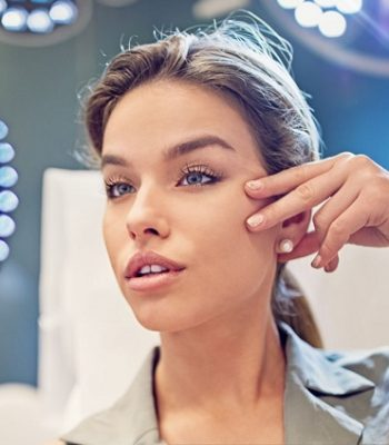 Young woman is looking her face in the mirror after beauty treatment procedure